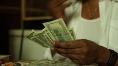 African American Male Counting Money, while smoking a Cigarette Stock Footage
