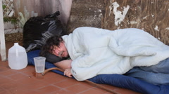 Homeless jobless sleeping on the floor drinks water Stock Footage
