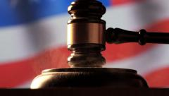 Judge calling order with hammer and gavel in american court with flag background Stock Footage