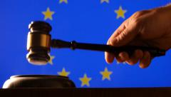 Judge calling order with hammer and gavel in EU court with flag background - stock footage