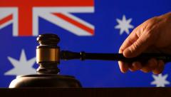 Judge calling order with hammer gavel in australain court with flag background Arkistovideo