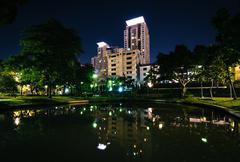 Pond at Santiphap Park and skyscrapers at night, in Bangkok, Thailand. - stock photo