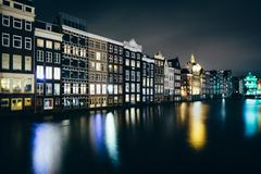 Buildings along the Damrak canal at night, in Amsterdam, The Netherlands. - stock photo