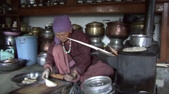 Traditional old woman making bread over old stove in kitchen Stock Footage