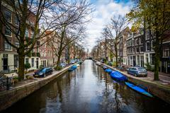 Boats and buildings along a canal in Amsterdam, Netherlands. - stock photo