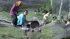 Traditional dressed young children washing dish in creek in the Himalayas Stock Footage
