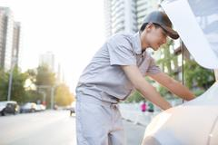 Auto mechanic repairing car Stock Photos