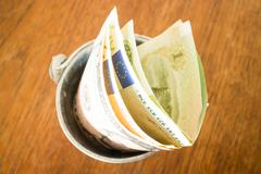 International currencies bank note in the bucket - stock photo