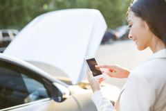 Female driver messaging on mobile phone next to broken down car Stock Photos