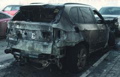 Accident or arson burnt car on the road - stock photo
