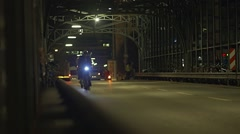Bicyclists moving evening illuminated metal bridge in slow motion Stock Footage