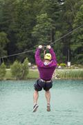 Muscled man on zip line - stock photo