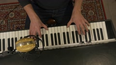 Unique shot of Man playing keyboard from above paning Stock Footage