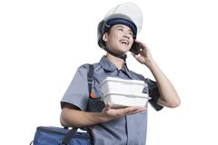Take-out deliveryman talking on the phone - stock photo