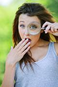 funny girl with loupe - stock photo