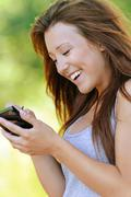 Smiling young woman writing on device Stock Photos