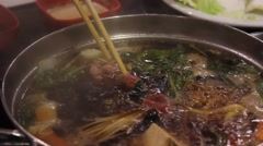 Cooking a piece of meat on Shabu Shabu hot pot Stock Footage