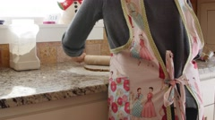 Woman rolling out dough to make gingerbread men Stock Footage