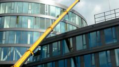 Tall crane reconstruct modern glazed building in the city Stock Footage