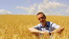 View of young handsome man sits in the wheat field - happy, joy, cheer, emotions Stock Footage