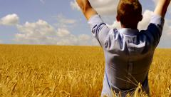 Young handsome man rejoices magic moment -view of his back in the field of wheat Stock Footage