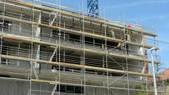 View of the large scaffolding by the building in the city - sunny day - blue sky Stock Footage