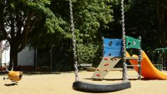 View of the kid playground in the suburb - swing swings at the moment  Stock Footage