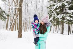 Happy family mother and child baby daughter on a winter walk in the woods Stock Photos