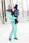 Stock Photo of happy family mother and child baby daughter on a winter walk in the woods