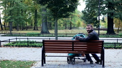 Happy man with stroller relaxing on bench in the park - stock footage