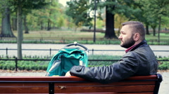 Sleepy, tired man with stroller yawning on bench in the park Stock Footage