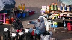 Morocco women drink tea in the market of Marrakesh Stock Footage
