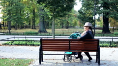 Angry woman with stroller talking on cellphone on bench in the park Stock Footage