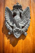 The door to the house with the emblem of an eagle on the shield - stock photo