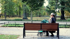 Woman with stroller relaxing in the park - stock footage