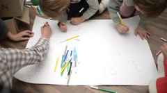 Children draw with markers on a large paper Stock Footage