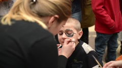 Body art artist draws on the boy's face - happy children - stock footage