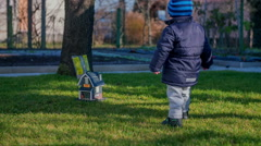 A little child is walking up to a small wooden house that is on the ground Stock Footage