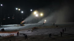Stock Video Footage of Skiers ride on the ski slopes and snow cannons