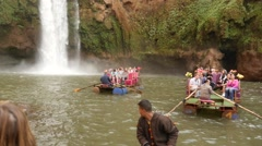 Tourists in boats in a pond at Ouzoud waterfall slow motion Stock Footage