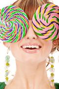 Lovely girl closes eyes two lolipops Stock Photos