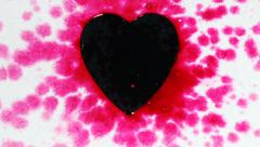 Pink color drops and splatters on black heart Stock Footage