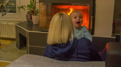 Happy child is jumping on his mom's lap Stock Footage