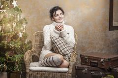 Beautiful woman drinking tea or coffee sitting in a chair with pillows in the Stock Photos