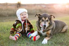 Happy Baby Bundled up Outside in Winter with Pet Dog - stock photo