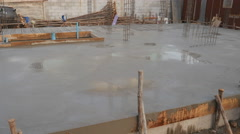 Panning shot of wet cement floor in building construction site Stock Footage