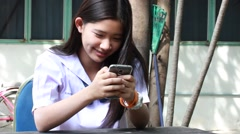 Thai student teen beautiful girl using her phone and smile. Stock Footage