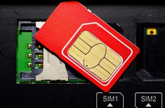 Red SIM card on slots in mobile phone. Stock Photos