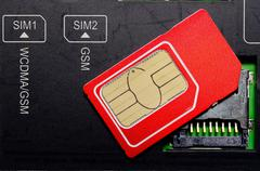 Red SIM card on slots in mobile phone. - stock photo