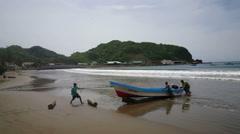 Fishermen pushing boat ashore Stock Footage
